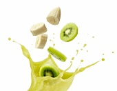 A splash of kiwi juice with slices of kiwi and banana