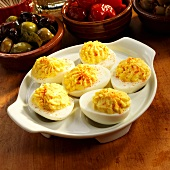 Dish of Deviled Eggs with Olives and Peppers in the Background