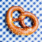 A pretzel on a blue and white tablecloth