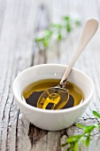 A bowl of olive oil with a spoon
