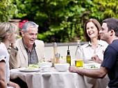 Family sitting having lunch in garden