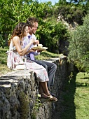 Hochzeitsgäste essen Kuchen auf einer Gartenmauer