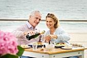 Paar beim Essen in einem Restaurant am Meer