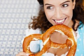 Young Woman Eating Huge Pretzel