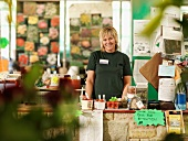 Female Garden Center Worker Behind Till