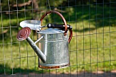 Watering Can and Trowel Hanging on Metal Fence