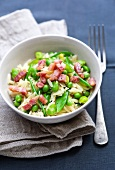A bowl of orzo pasta with peas, broad beans and bacon