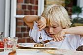 Blonder Junge isst Bratwurst mit Messer & Gabel