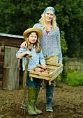Mutter & Tochter im Garten mit Kiste frisch geernteter Kartoffeln