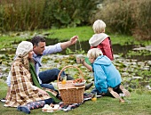Familie beim Picknick an kleinem Teich im Herbst