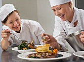Two female chefs finish some dinners