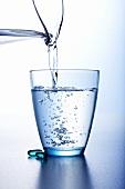 Wasser aus Krug in ein Glas gießen