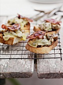 Gratinated toast slices with mushrooms, cheese and bacon