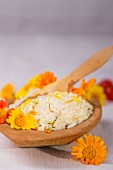 A wooden bowl with rice garnished with marigolds