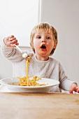 2 year old boy eating spaghetti
