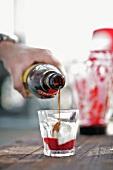 Mann giesst Drink in ein Glas