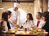 Chefkoch bedient Menschen im Restaurant
