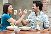 Couple feeding each other spaghetti