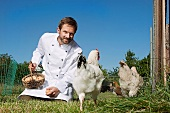 Chef feeding chickens outdoors