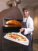 Pizza chef holding pizza in front of oven