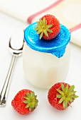 Natural yogurt in a glass surrounded by fresh strawberries