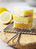Three Lemon Bars Topped with Powdered Sugar Stacked on a Plate