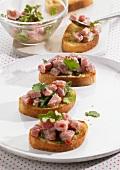 Crostini topped with raw tuna salad