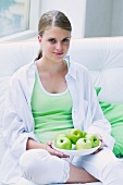 A girl holding a plate of green apples