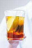 A glass of tea with a lemon wedge and a tea bag