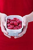 A girl holding a plastic bowl of raspberries