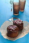 Mini chocolate cakes decorated with sugar hearts on a blue wooden table