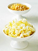 Bowl of Popcorn with a Bowl of Popcorn Kernels in the Background