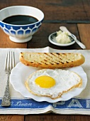 Fried Egg with a Piece of Country Bread Toast and a Cup of Black Coffee