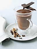 Glass Mug of Hot Chocolate with a Piece of Dark Chocolate and Spices