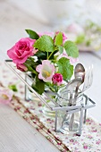 Table decoration with pink roses, bell flowers and lemon balm