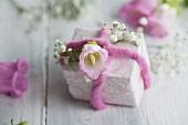 Päckchen mit Schleierkraut, Glockenblumen und fliederfarbenem Filzband