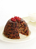 Christmas puddings with redcurrants, sliced