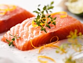 A raw salmon fillet on a bed of salt with lemon zest and dill flowers