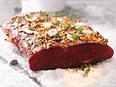 Raw beef loin with a mustard and garlic marinade on a bed of salt