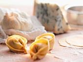Fresh tortellini with gorgonzola cheese in the background