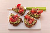 Crostini topped with guacamole, ham and cherry tomatoes