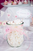 A jar of mini marshmallows decorated with a pink ribbon