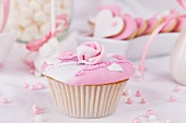 A cupcake with pink and white glaze, sugar roses and sugar pearls