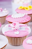 Cupcakes with pink and white glaze and sugar roses