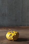 An ornamental yellow squash on a wooden table