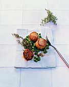 Scallops with peas and thyme cooked in a frying pan