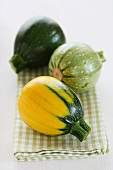 Mini courgettes in three colours on a tea towels