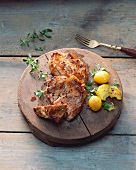 Pork steaks with potatoes on a wooden board