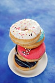 Four doughnuts with colourful glaze and sugar sprinkles