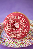 A doughnut with raspberry glaze and sugar sprinkles